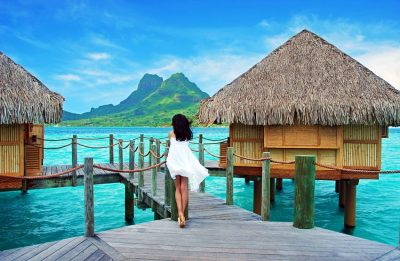 A wooden pier next to a body of water with Bora Bora in the background