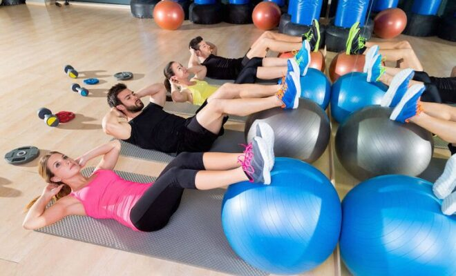 A group of people doing workout in gym
